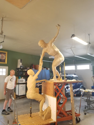 "Columbine Gallery and the National Sculptors' Guild are pleased to team up with the Rotary Club of Thompson Valley on ""The Legacy Project"" in Loveland, Colorado.   The Legacy Project celebrates the 30th anniversary (2019) of the Rotary Club of Thompson Valley. The bronze sculpture depicts a woman helping a teenage boy surmount a stone precipice tying into the Rotary motto, ""Service Above Self"". Part of this service has been the club's support of Polio Plus, a major contributor to the eradication of Polio world-wide.  ""Reaching our Goal"" by NSG Fellow Denny Haskew will be placed in the plaza of The Foundry, a new development that is transforming Loveland's historic downtown, set to open Fall 2018. The art placement will coincide with the opening.  The National Sculptors' Guild designed additional stone elements to activate the plaza and provide area's of recognition to the club's efforts.   We have contributed $50,000 to the project, our way of giving back to the support we've received from this community over the past 26 years.   Haskew is a renowned figurative artist and a Charter Member of the National Sculptors' Guild. His work is in the numerous prestigious collections including the Smithsonian Institution, the Gilcrease Museum, OK and the Boulder and Colorado Springs campuses of the University of Colorado.  ​Denny Haskew currently resides in Loveland, Colorado where he is actively engaged in the art industry as a sculptor. He received his degree from the University of Utah, then served two years in the United States Army during the Vietnam War.   Having spent numerous years as a guide and ski instructor, Denny has learned to love the rivers and mountains of the western states of Arizona, Colorado, Idaho, Oregon, and Utah.  After moving to Loveland, a hub of successful working sculptors, he wasted no time in getting monumental sculpture experience through working with renowned sculptors including Fritz White and Kent Ullberg.  Since 1987, Denny has created and placed dozens of monumental compositions; spanning the spectrum of the figurative genre."