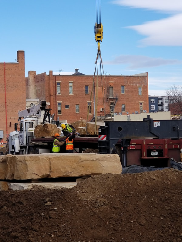 "Update 11/16/2018: Today was a huge step in the installation of The Legacy Project. Over 68,000 lbs of Dakota sandstone was craned into the site and set by Denny Haskew and the National Sculptors' Guild. Next week the final stone and bronze element will be placed.  The Rotary Club of Thompson Valley's ""Legacy Project"" will activate the plaza of The Foundry, a new development that is transforming Loveland's historic downtown. The installation includes ""Reaching Our Goal"" bronze sculpture by National Sculptors' Guild Charter Member Denny Haskew"