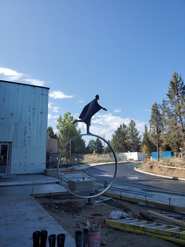 "Installed Today! The National Sculptors' Guild completed installing Carol Gold's bronze sculpture ""Time"" in Bend, Oregon earlier today. Below are some images from the installation.  ""Time"" depicts a stylized figure running atop a large wheel, alluding to travel, as well as, the ceaseless movement of the clock. The implied motion of the sculpture reflects the energetic and playful mood of city life. ​ The bronze figure measures 6 feet high, 4.5 feet wide and 3.5 feet deep. The 7-ft diameter circular ring will be fabricated from rectangular rolled stainless steel tubing.   More images to follow once landscaping is complete."