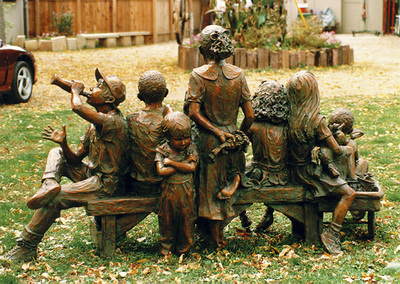 "National Sculptors' Guild public art placement 36 Jane DeDecker's Snapshot multicultural figurative bronze sculpture Oxnard, California 1995 ""Snapshot"" by Jane DeDecker and the National Sculptors' Guild was placed in Oxnard, California in 1995.   ​Snapshot was originally commissioned by Michael Jackson, The multi-figure bronze depicts a number of children ready for the camera, sitting on a bench with a wagon pulled up to one side; the kids are in a casual pose, enjoying a respite from summer play, holding toys and drinking a soda. It even includes the pouting kid in the back - not wanting to be pictured as often happens. The piece is universal even though it was inspired by photos Jackson gave DeDecker.   NSG Public Art Placement 36"