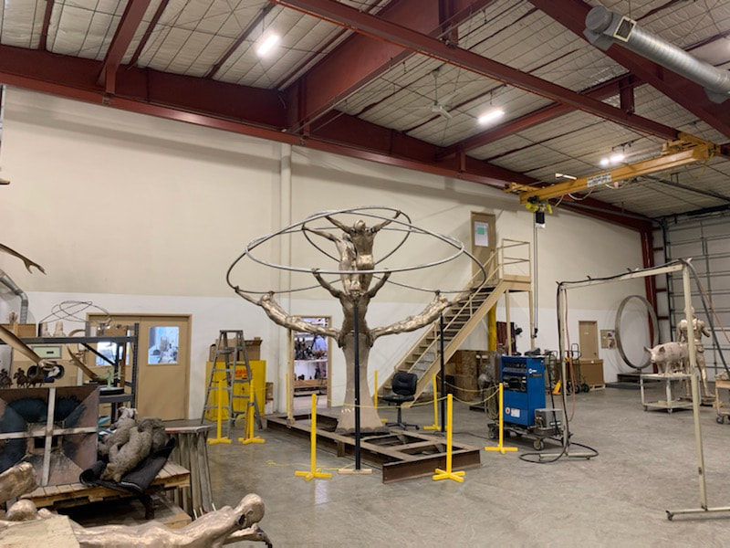 "Coming soon to Downey, California... ​""Tree of Life"" by Clay Enoch and the National Sculptors' Guild is in the finishing steps of bronze casting at Art Castings of Colorado.  This installation is part of a series of Public Art placements that the City has commissioned from the National Sculptors' Guild for installations in 2020. The bronze and stainless steel sculpture will be placed in a 18-foot diameter fountain at the Theater Plaza.  Our design team began working on this project in March of 2019.  Measuring 12-feet tall and 14-feet in diameter, the tree composed of eight life-size bronze figures out stretched from a single column are united by the stainless steel rings they hold; this sculpture is among our most complex figurative monuments to date. We are so excited to see this significant art statement in place. We will update this post as soon as installation is set.  Progression of the project is shown below..."