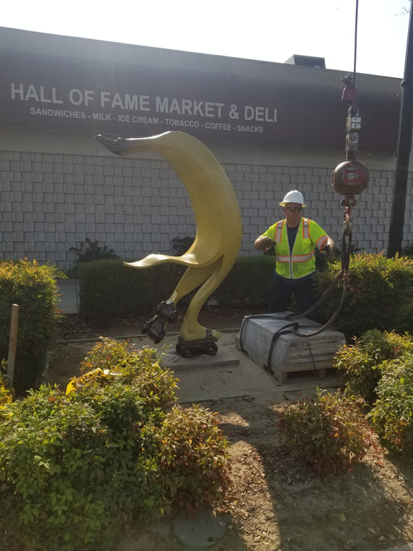 "The National Sculptors' Guild has installed Affiliate Jack Hill's ""On a Roll"" in Downey, California. We're thrilled with this playful public art placement, appropriately placed adjacent to the Hall of Fame Market and Deli. We hope you find it a'peeling'.  This installation is part of a series of Public Art placements that the City has commissioned from the National Sculptors' Guild to enhance ​Downey Avenue.  ​Special thanks to NSG Fellow Clay Enoch, Capitol Crane and the City of Downey for the installation help.  ​NSG Public Art Placement #521"