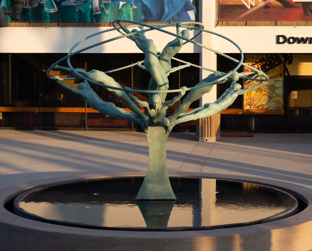 "A few more photos from our ""Tree of Life"" installation in California. ""Tree of Life"" by Clay Enoch and the National Sculptors' Guild is in its new home at the center of the new Downey Theatre Plaza fountain. The 14-foot bronze and stainless-steel sculpture features 8 life sized figures gracefully stretching out from a single column and united by huge intersecting rings.  NSG Public Art Placement 524 See more of the entire process here...  http://www.jk-designs-inc.com/.../tree-of-life-in-Downey-ca Special thanks to our Colorado and California team members! Tony Workman and the Art Castings of Colorado staff, Dennis Henderson of DC Crane, John Eisenman Transportation, Zach Pennington of Blackeagle Fabrication, Jim Lambert and Shippers' Supply, Western Steel, Russ Martino and Adam Granath of Martino & Luth, Josef Kekula and the City of Downey, Capital Crane, Andy Garza of Pacific Wood and Iron, and of course Clay Enoch and John Kinkade of the National Sculptors' Guild."