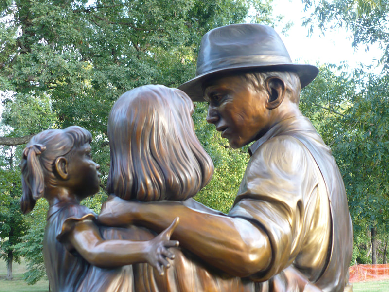 """A Prosperous Past, a Bright Future"" by Fellow Gary Alsum and the National Sculptors' Guild was placed in Brighton, CO at Bridge St and Cabbage Ave.  ​The public artwork features two sculptural elements. The first element speaks to Brighton's rich history and sense of family. The piece depicts a father, mother and young daughter. The father's occupation is vague so that the viewer could see him as a farmer, a miner or any profession that made Brighton what it is today. On the ground next to the mother's foot is a basket of vegetables, a nod to Brighton's agricultural past and future. The second element connects to the city's current boom and its continued success in the future. This sculpture depicts a young boy, playing with a train and a toy airplane. The train is symbolic of Brighton's past. The airplane is symbolic of Brighton's steady economic growth as a result of its proximity to DIA. Gary states that ""The challenge of sculpture is depicting the movement and energy of a single moment."" Placing a great deal of focus on movement and grace, Gary's sculptures pass on the freedom, joy and curiosity that children display on a daily basis. ​  NSG Public Art Placement #287"