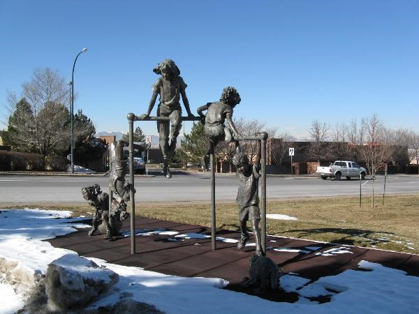"The National Sculptors' Guild placed Fellow Jane DeDecker's ""Jungle Gym"" in Westminster, Colorado in 1995. The 125% life-size multi-figurative bronze features five-children at play on a jungle gym, joined in by a dog tugging at the laces of one of the kids. The piece is a reminder of simpler days of play in parks and schools.   The sculpture measures 11ft tall, 15ft wide, 5ft deep.  NSG public art placement 9"